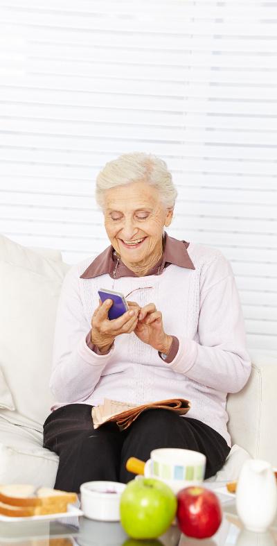 Lächelnde Seniorin liest eine Nachricht auf ihrem Smartphone